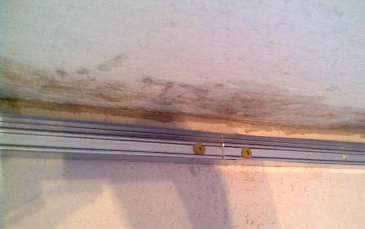 Потолочный направляющий профиль на стене, зафиксированный дюбель-гвоздями