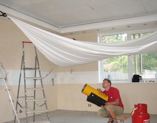 Нагревание строительным феном полотна для фиксации на потолке